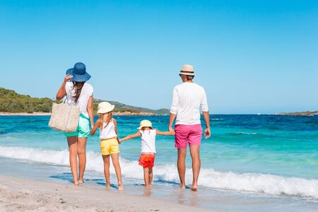 Photo for Happy beautiful family on white beach. Back view. - Royalty Free Image