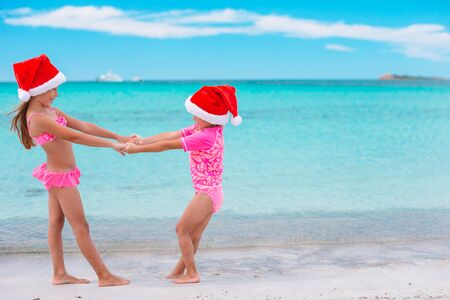 Photo pour Little adorable girls in Santa hats during beach vacation have fun together - image libre de droit
