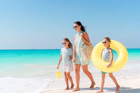 Photo for Adorable little girls and young mother on white beach. Family on the beach ready to swim - Royalty Free Image