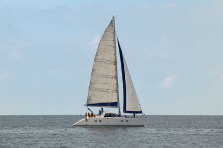 Photo pour Sailboat in profile with some people on board and a Germany flag on the side - image libre de droit