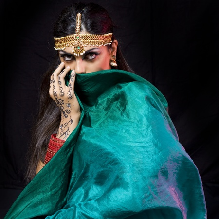 young beautiful oriental style woman covering herself with a green veil