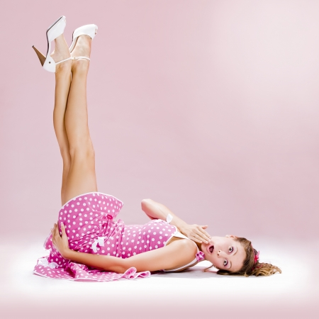 a beautiful inocent pin-up girl over a pink background