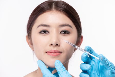 Photo pour Surgery concept. The doctor cosmetologist makes the Rejuvenating facial injections procedure for tightening and smoothing wrinkles on the face skin of a beautiful. - image libre de droit