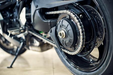 Photo pour Detail of a motorcycle rear chain with exhaust pipes. Rear view of a motorcycle with the focus on chain. - image libre de droit