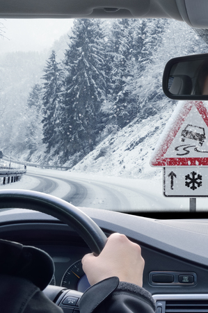 Photo pour Winter Driving - Snowy Road with Warning Sign - image libre de droit