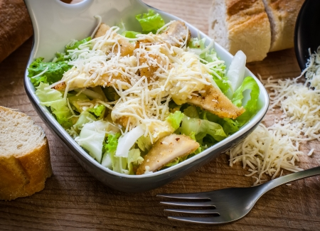 fresh caesar salad on bowl with parmesan cheese