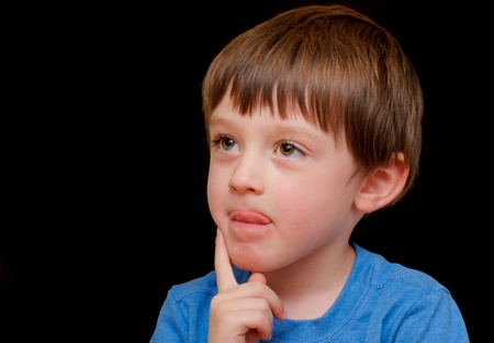 A curious four year old boy on a black background