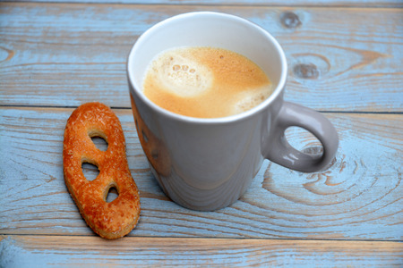 Coffee with pretzel cookie on a wooden background