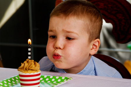 Child trying to blow out candle on cupcake