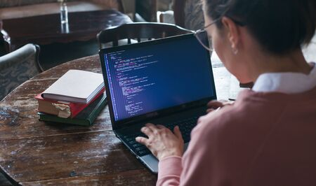 Foto de Hacking system. An excited girl with dark hair and in a pink sweater and glasses writes code on a laptop while sitting in a library. Work undercover. Girl hacker. View from the shoulder. - Imagen libre de derechos