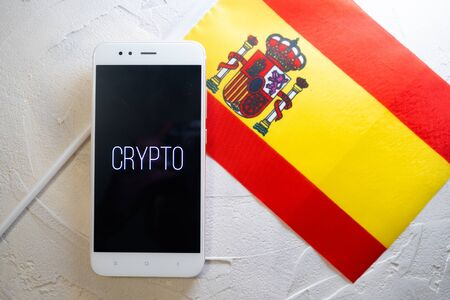Cryptocurrency and government regulation, concept. Modern economy, smartphone with bitcoin sign on the screen on the background of the flag of Spain