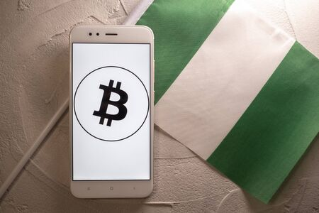 Cryptocurrency and government regulation, concept. Modern economy, smartphone with bitcoin sign on the screen on the background of the flag of Nigeria