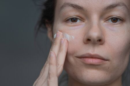 Photo for Skin care, portrait of a young beautiful woman close-up, without makeup and retouching. health of the skin and face care, concept. Trending portrait showing real skin, young woman using face cream - Royalty Free Image