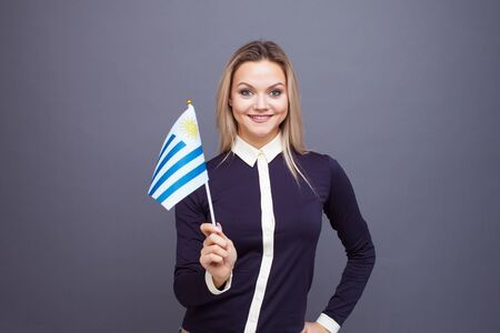 Photo for Immigration and the study of foreign languages, concept. A young smiling woman with a Uruguay flag in her hand. Girl waving a Uruguayan flag on a gray background - Royalty Free Image