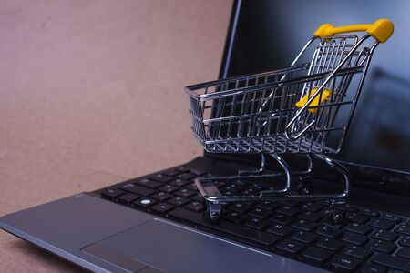 Photo pour End of online sales, concept. Online shopping, shopping cart on laptop keyboard. Shopping in online stores and online payments. An empty shopping cart rolling across the keyboard of a computer - image libre de droit