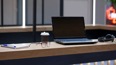 Photo pour Workplace with a laptop, Notepad and pen, in the distance are headphones and a cardboard coffee Cup, Desk for work, glasses on the table - image libre de droit
