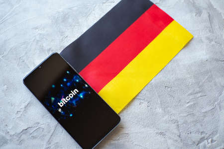 Cryptocurrency and government regulation, concept. Modern economy, smartphone with bitcoin sign on the screen on the background of the flag of Germany