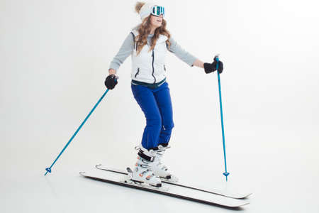Photo pour Skier maneuvers on mountain skis, photos on a white background in the Studio, winter sports, Hobbies and a healthy lifestyle. Young woman on skis in light winter clothing for outdoor activities - image libre de droit