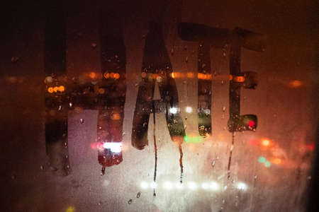 Photo pour Hate, negative emotions. Inscription on the fogged glass, night city on the background. image with tinting and noise effect - image libre de droit