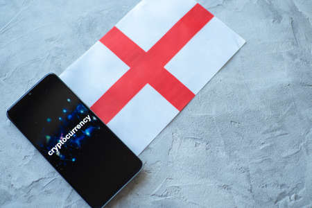 Cryptocurrency and government regulation, concept. Modern economy, smartphone with bitcoin sign on the screen on the background of the flag of England