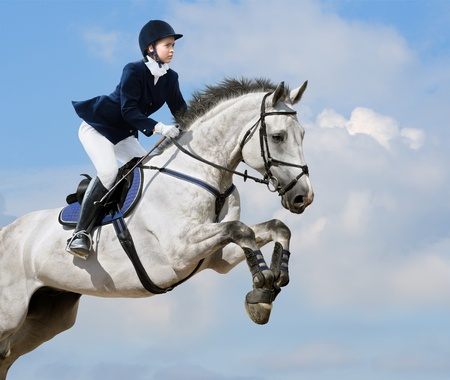 Young girl jumping with gray horse