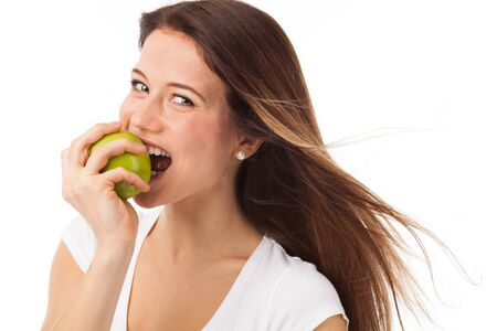 Young woman biting a green apple, isolated on white