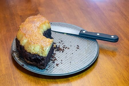 a cake and a knife on a platter on a table