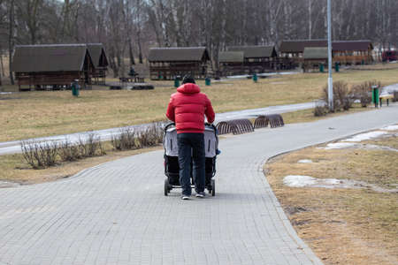Photo for A dad with a double pram strolls through a cold, deserted city park in early spring. A man in a bright red warm jacket. - Royalty Free Image