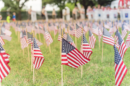 Photo pour Lawn American flags with blurry row of people carry fallen soldiers banners parade - image libre de droit