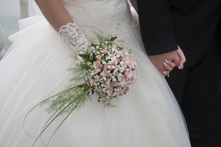 The hand of the bride holds a bouquet