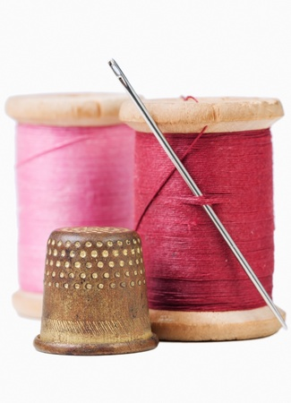 Old thimble and needle with pink and red  thread on white with shadow
