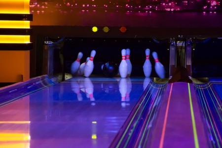 Ball does strike on ten pin bowling in skittle-ground of glow in the dark bowling