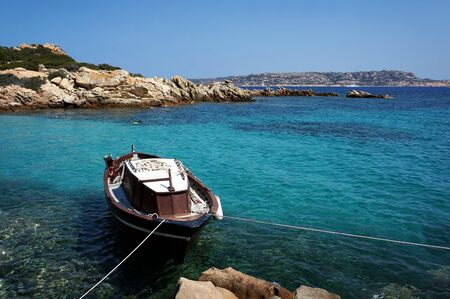 Photo pour Seascape with boat on vivid turquoise water. La Maddalena Archipelago in Sardinia, Italy.           - image libre de droit