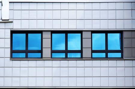 Photo pour Facade of modern building. Reflection of blue sky in windows glass. - image libre de droit
