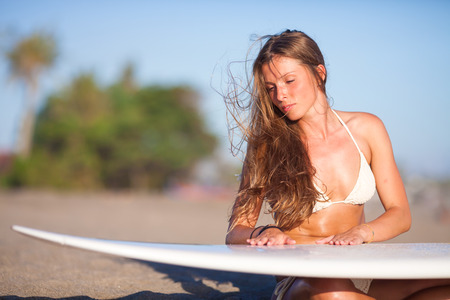 young girl with surfboard at the beach.Bali.Indonesia.
