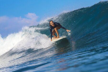 Photo pour Female surfer on a blue wave at sunny day - image libre de droit