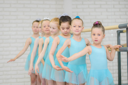 Photo pour Ballet school. Little girls students practicing near barre .Middle shot of ballerinas in dance class. - image libre de droit