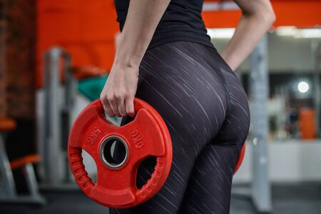 Foto de Slim, bodybuilder girl with sexy buttocks lifts heavy dumbbell, closeup. Woman with perfect big butt. Weight lifting concept. - Imagen libre de derechos
