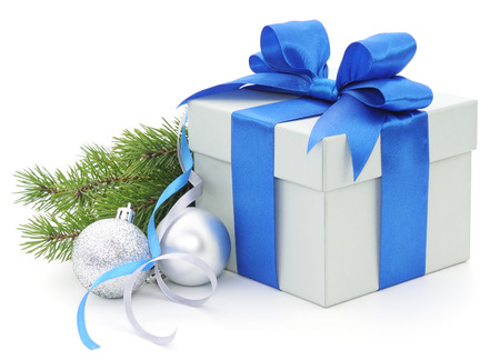 Christmas gift box with blue ribbon and fir branches.