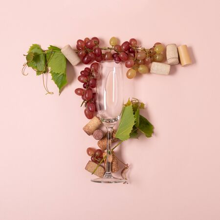 Foto de Alphabet. Letter T made of wineglasses with rose and white wine, grapes, leaves and corks lying on pink background. Wine degustation concept. Flat lay. Top view - Imagen libre de derechos