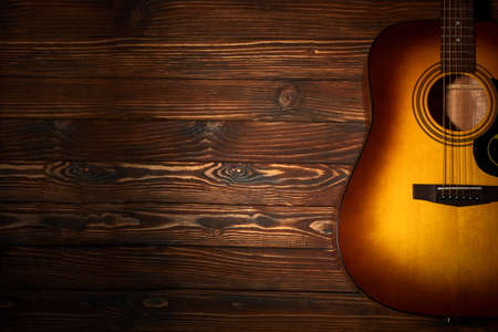 Acoustic guitar on wooden background. Copy space. Top view