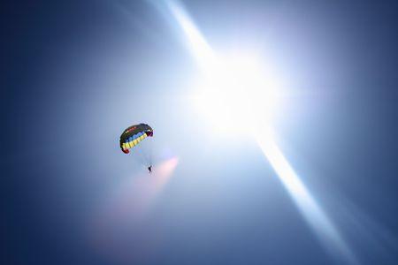 Parachutist at blue sky and bright sun rays