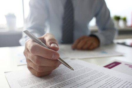 Photo pour Hand of businessman in suit filling and signing with silver pen partnership agreement form clipped to pad closeup. Management training course, some important document, team leader ambition concept - image libre de droit