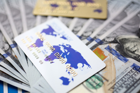 Huge pack of US money and bank card lying down on important financial document