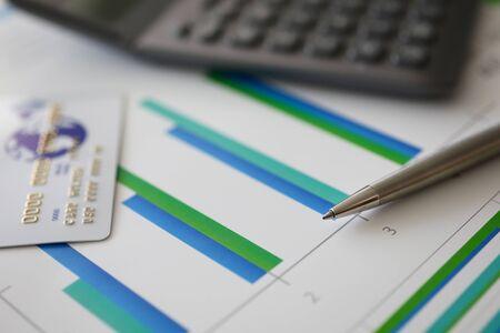 Photo pour Pen, calculator and plastic debit card on graph - image libre de droit