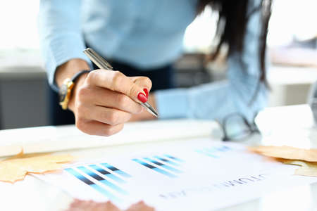 Photo pour Woman in office holds a pen in her hand over chart - image libre de droit