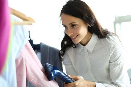Photo pour Smiling woman ironing her shirt with steamer in laundry - image libre de droit
