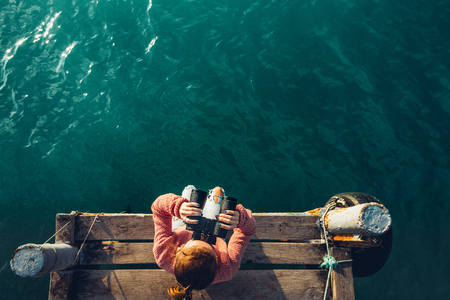 Photo pour Young Girl Sits On The Pier And Looks At Sea Through Binoculars, Top View. Adventure Vacation Discovery Travel Concept - image libre de droit