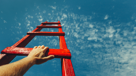 Photo pour Development Attainment Motivation Career Growth Concept. Mans Hand Reaching For Red Ladder Leading To A Blue Sky - image libre de droit