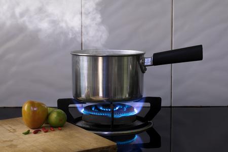 Foto de Hot steam on Metal pot on the flame gas stove for boiling water Soup. - Imagen libre de derechos